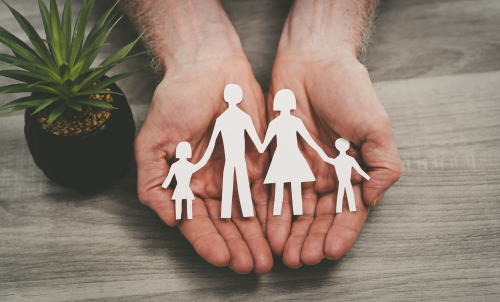 person cupping paper cutout of family in hands